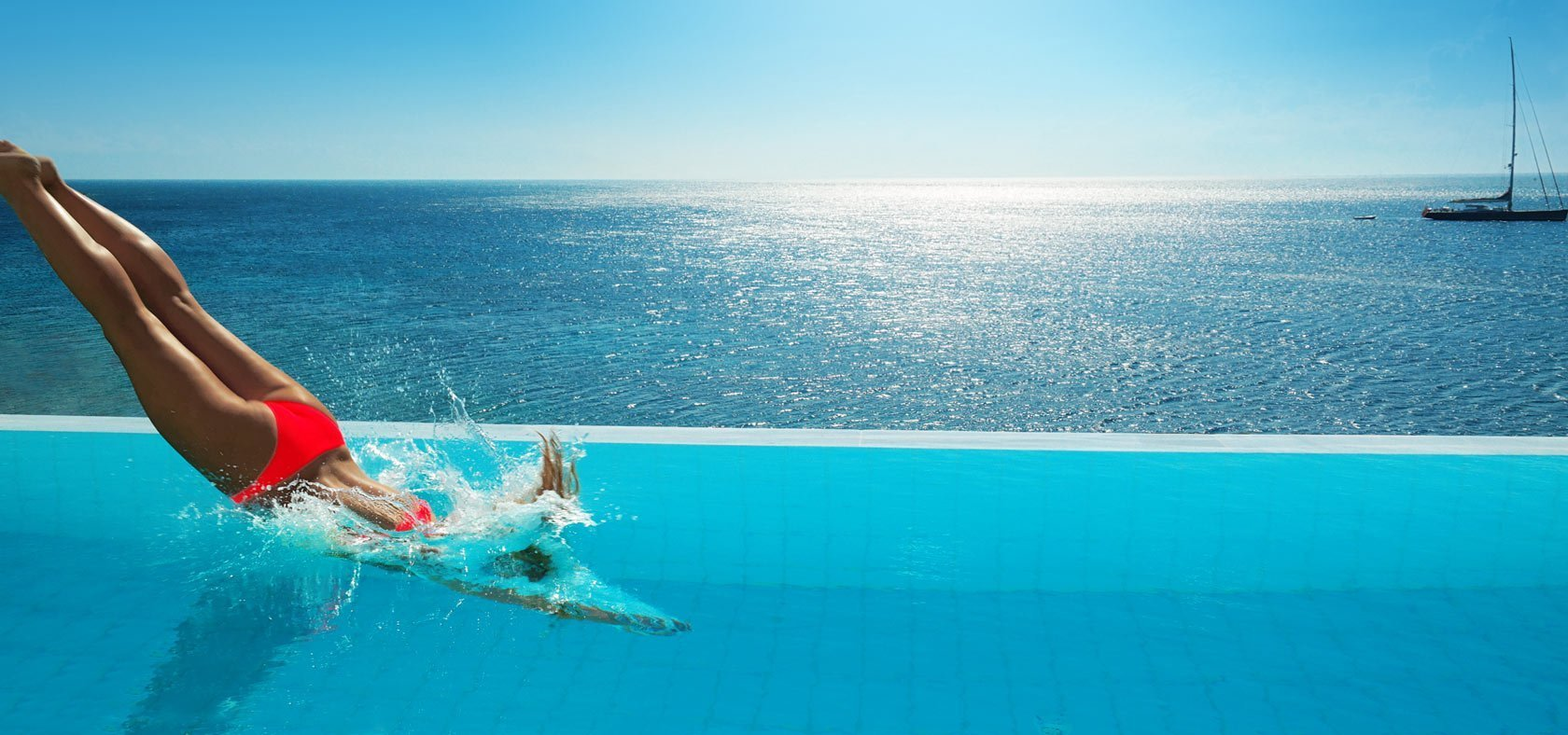 Lady in a red swimsuit diving into the infinity pool with sea views at Petasos Resort & Spa Mykonos.
