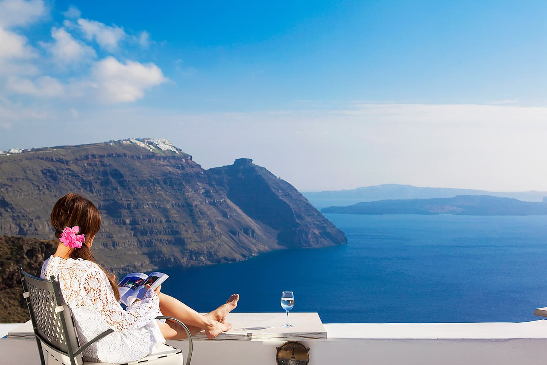 Lady on a balcony at San Antonio Santorini overlooking the Aegean sea.