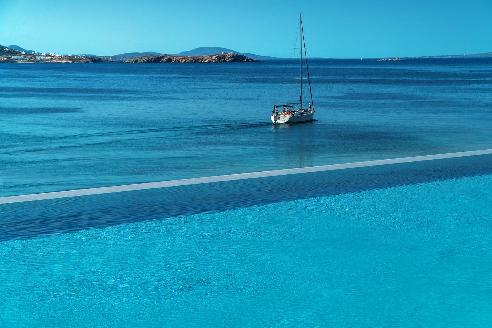 The infinity crystal clear pool at Mykonos Riviera overlooking the Aegean sea.
