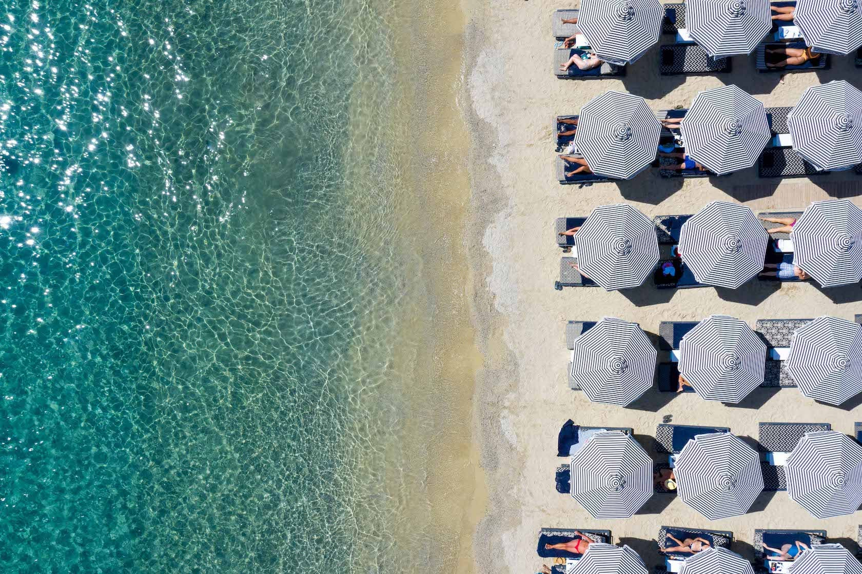 Overhead view of sun umbrellas and the beach of Ornos in Mykonos.