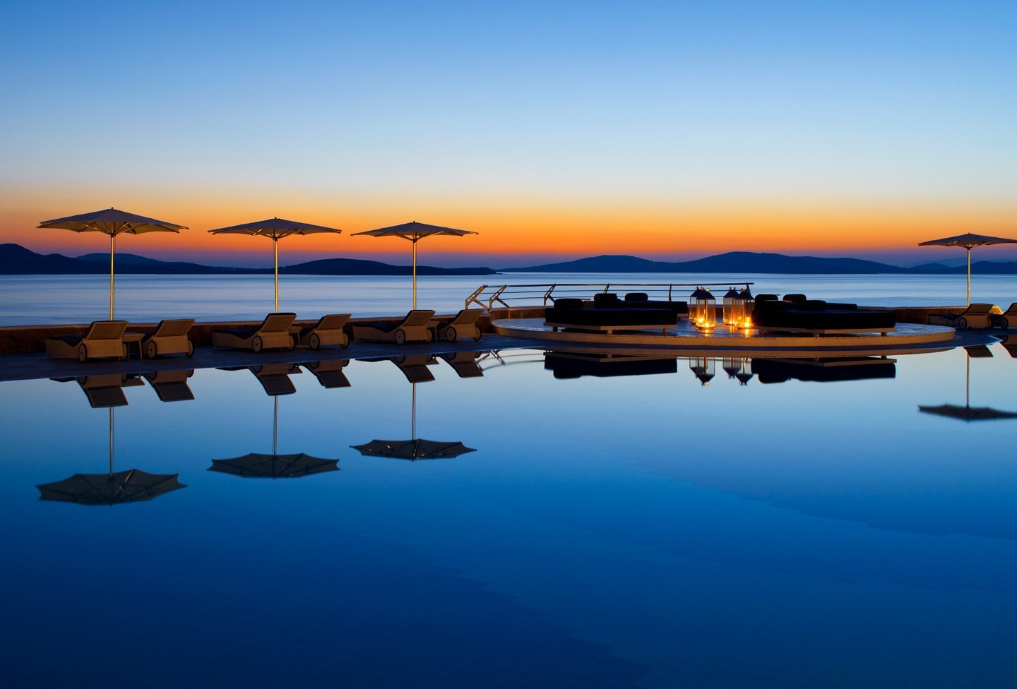Sunbeds by the crystal clear swimming pool overlooking the Aegean sea at sunset.