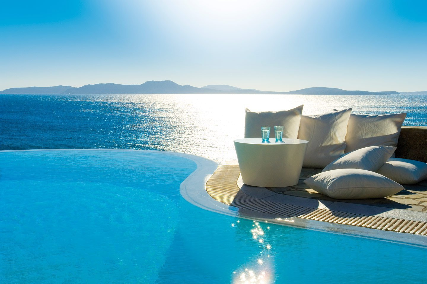 Glasses on a modern coffee table by the infinity pool overlooking the sea at Mykonos Grand Hotel.