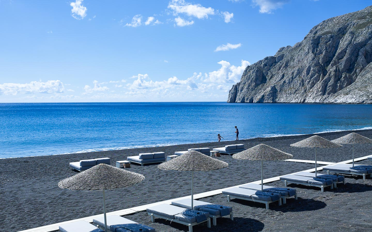 Sunbeds and umbrellas on the beach in Santorini. Crystal clear sea and imposing rocks.
