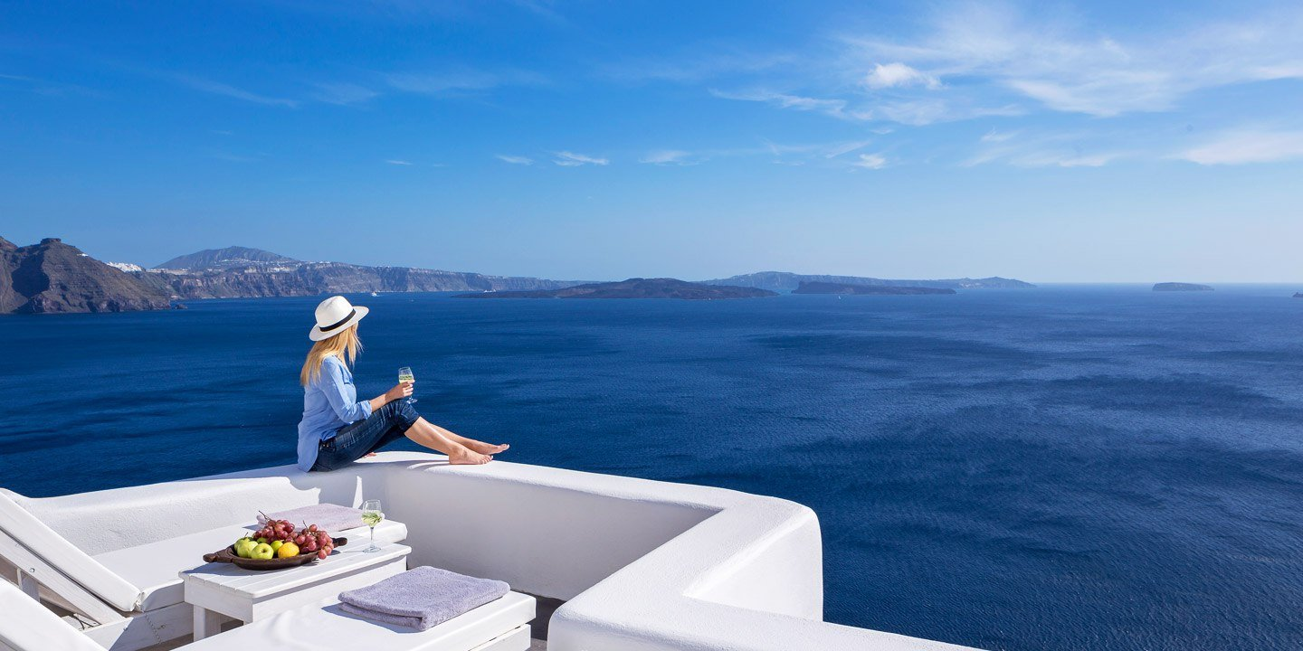 Lady by the edge of a private balcony in White Pearl Villas Santorini overlooking the sea.