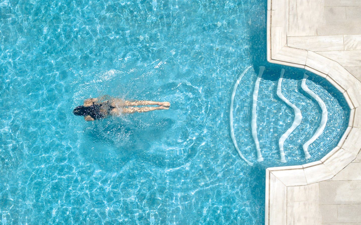 Overhead view of a lady swimming in the crystal clear pool in Harmony Hotel.