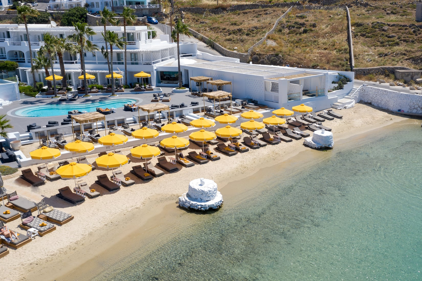 Umbrellas and sunbeds on the beach in front of Mykonos Blanc Hotel.