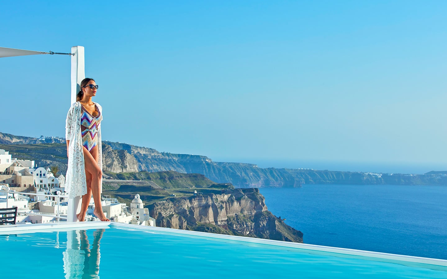 Lady standing by the edge of the infinity pool at Cosmopolitan Luxury Suites Santorini.